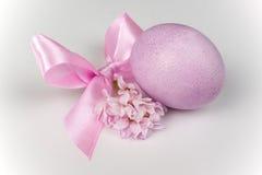 Uovo di Pasqua rosa con l'arco del nastro e fiore isolato su bianco Fotografia Stock
