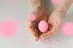 Uovo di Pasqua rosa in mani su fondo bianco Fotografia Stock