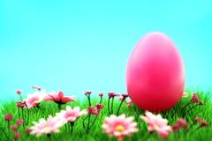 Uovo di Pasqua rosa sul prato con i fiori & il ciano fondo Immagini Stock Libere da Diritti