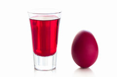 Uovo di Pasqua rosso con un vetro della bevanda Fotografia Stock