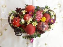 Uovo di Pasqua rosso ornato con i fiori selvaggi e le erbe freschi fotografie stock libere da diritti