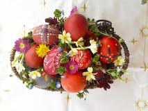 Uovo di Pasqua rosso ornato con i fiori selvaggi e le erbe freschi immagine stock