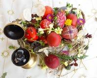 Uovo di Pasqua rosso ornato con i fiori selvaggi e le erbe freschi fotografia stock libera da diritti