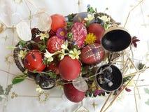Uovo di Pasqua rosso ornato con i fiori selvaggi e le erbe freschi immagini stock libere da diritti