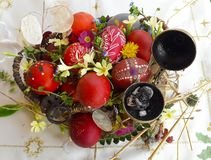 Uovo di Pasqua rosso ornato con i fiori selvaggi e le erbe freschi fotografie stock