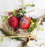 Uovo di Pasqua rosso ornato con i fiori selvaggi e le erbe freschi fotografia stock