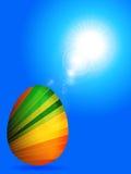 Uovo di Pasqua a strisce sopra cielo blu soleggiato Fotografia Stock Libera da Diritti