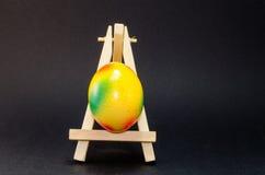 Uovo di Pasqua sull'artista Easel, fondo nero Fotografia Stock