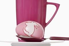 Uovo dipinto del eatser sul cucchiaio davanti alla tazza Fotografia Stock Libera da Diritti