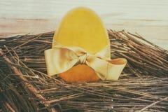 Uovo dorato con l'arco del regalo Fotografia Stock