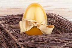 Uovo dorato con l'arco del regalo in nido Immagini Stock Libere da Diritti