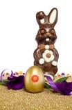 Uovo dorato di Pasqua con il coniglietto del cioccolato sopra bianco Fotografia Stock Libera da Diritti