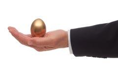 Uovo dorato in palma della mano Fotografia Stock