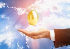 Uovo dorato sopra la mano maschio Immagine Stock