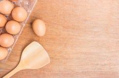 Uovo e spatola di legno su fondo di legno Fotografia Stock