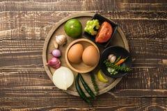 Uovo e spezia per il cuoco in buona salute sul fondo di legno della tavola nel principale v Fotografia Stock Libera da Diritti