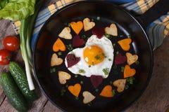Uovo e verdure sotto forma di cuore Fotografia Stock