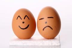 Uovo felice & triste nella priorità bassa bianca isolata Fotografia Stock