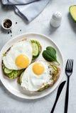 Uovo fritto, avocado e cetriolo su pane tostato intero grano fotografie stock