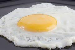 Uovo fritto in banda nera Fotografia Stock