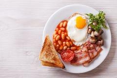 Uovo fritto con bacon, i fagioli e la vista superiore orizzontale del pane tostato Immagine Stock