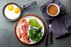 Uovo fritto della prima colazione Ketogenic di dieta, bacon ed avocado, spinaci e caffè a prova di proiettile Prima colazione ad  immagine stock libera da diritti