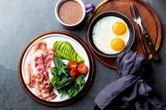 Uovo fritto della prima colazione Ketogenic di dieta, bacon ed avocado, spinaci e caffè a prova di proiettile Prima colazione ad  fotografie stock libere da diritti