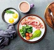 Uovo fritto della prima colazione Ketogenic di dieta, bacon ed avocado, spinaci e caffè a prova di proiettile Prima colazione ad  immagine stock