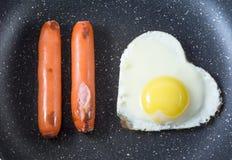 Uovo fritto della prima colazione in salsiccie in forma di cuore e arrostite nella pentola, vista superiore, Fotografia Stock