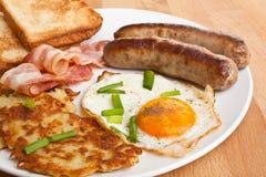 Uovo fritto, patate grattugiate/in padella e prima colazione del bacon Fotografia Stock