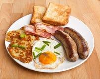 Uovo fritto, patate grattugiate/in padella e prima colazione del bacon Fotografie Stock
