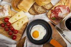 Uovo fritto in pentola, formaggio, prosciutto, pane e panini immagine stock