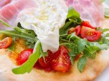 Uovo fritto, razzo e pomodoro con il prosciutto gastronomico immagini stock libere da diritti