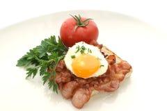 Uovo fritto su pancetta affumicata cotta Immagini Stock