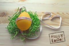 Uovo giallo in treccia su fondo di legno fotografie stock