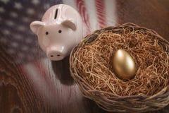 Uovo, nido e porcellino salvadanaio dorati con la riflessione della bandiera americana Fotografia Stock Libera da Diritti