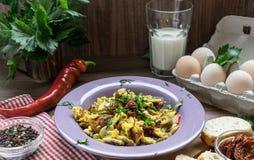 Uovo rimescolato con i pomodori e le merci al forno secchi della casa fotografia stock