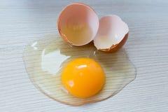 Uovo rotto del pollo sulla tavola immagine stock