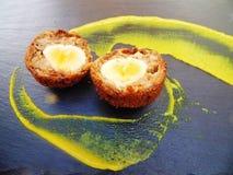 Uovo sodo/carne per salsiccia diviso in due con senape gialla sul piatto dell'ardesia fotografia stock