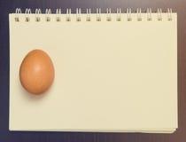 Uovo su un taccuino in bianco fotografia stock libera da diritti