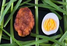 Uovo, taglio e lattuga su un fondo nero, primo piano immagini stock