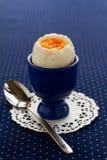 Uovo in un portauovo blu Fotografia Stock