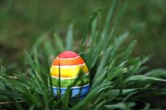 Uovo variopinto dell'arcobaleno di Pasqua sul fondo dell'erba verde Immagini Stock
