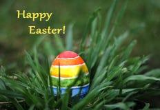 Uovo variopinto dell'arcobaleno di Pasqua sul fondo dell'erba verde, cartolina d'auguri Fotografia Stock