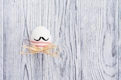 Uovo variopinto divertente con i baffi su fondo di legno Immagine Stock Libera da Diritti