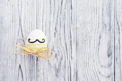 Uovo variopinto divertente con i baffi su fondo di legno Fotografia Stock