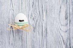 Uovo variopinto divertente con i baffi su fondo di legno Fotografie Stock