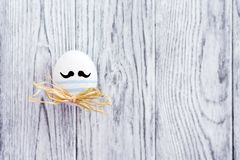 Uovo variopinto divertente con i baffi su fondo di legno Fotografia Stock Libera da Diritti