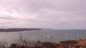 Upływu strzał plaża z skałami, piaskiem, fala i szybkim chodzeniem, chmurnieje zbiory