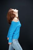 Up. Girl,in blue jeans and blue blouse posing, on black background stock images
